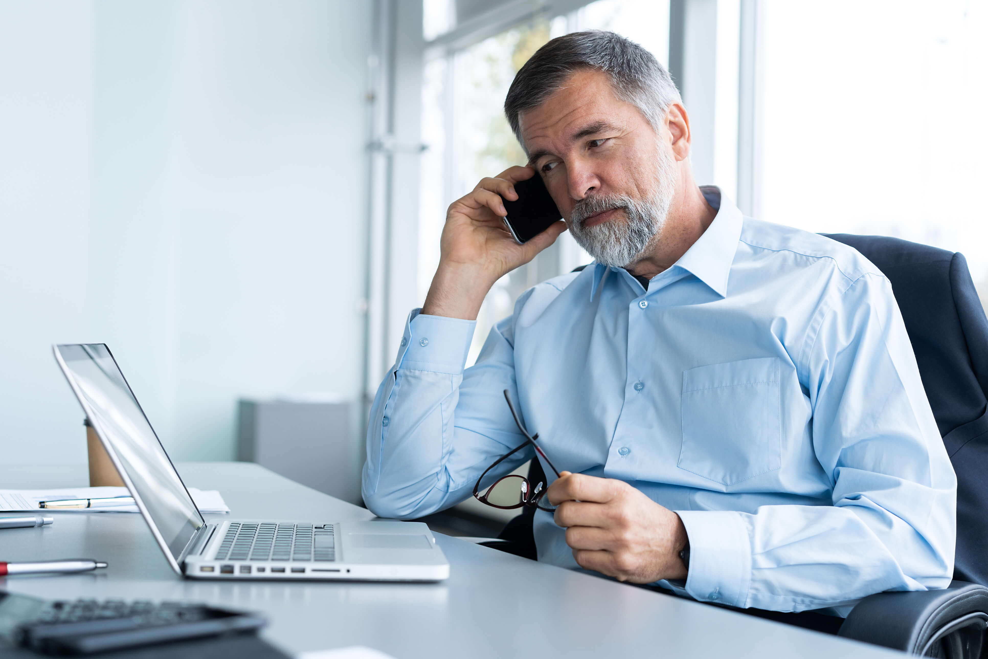 A man working on a laptop while talking in the phone