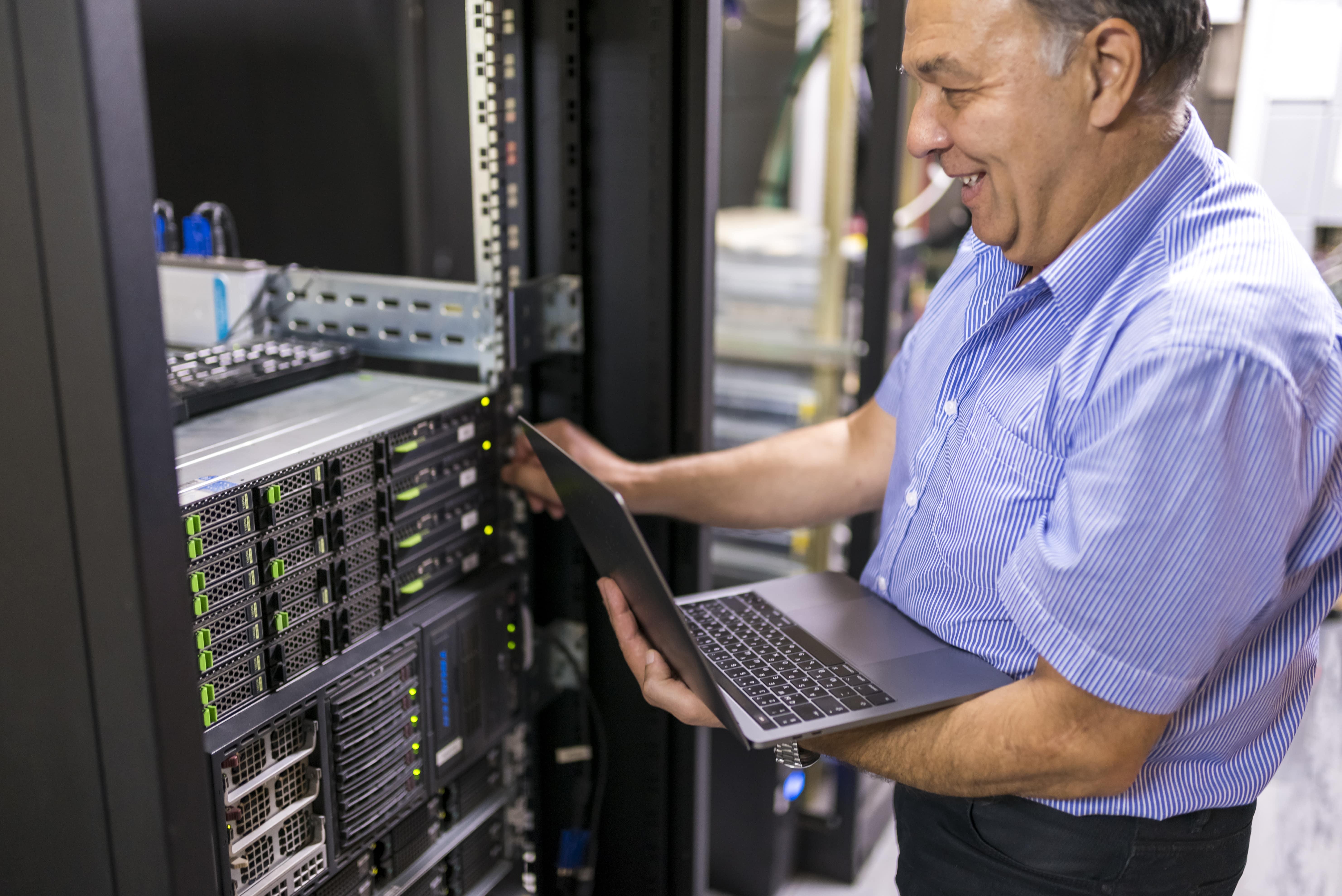 Illustrasjonsbilde. En mann stående ved en rekke servere med en laptop i hånden.
