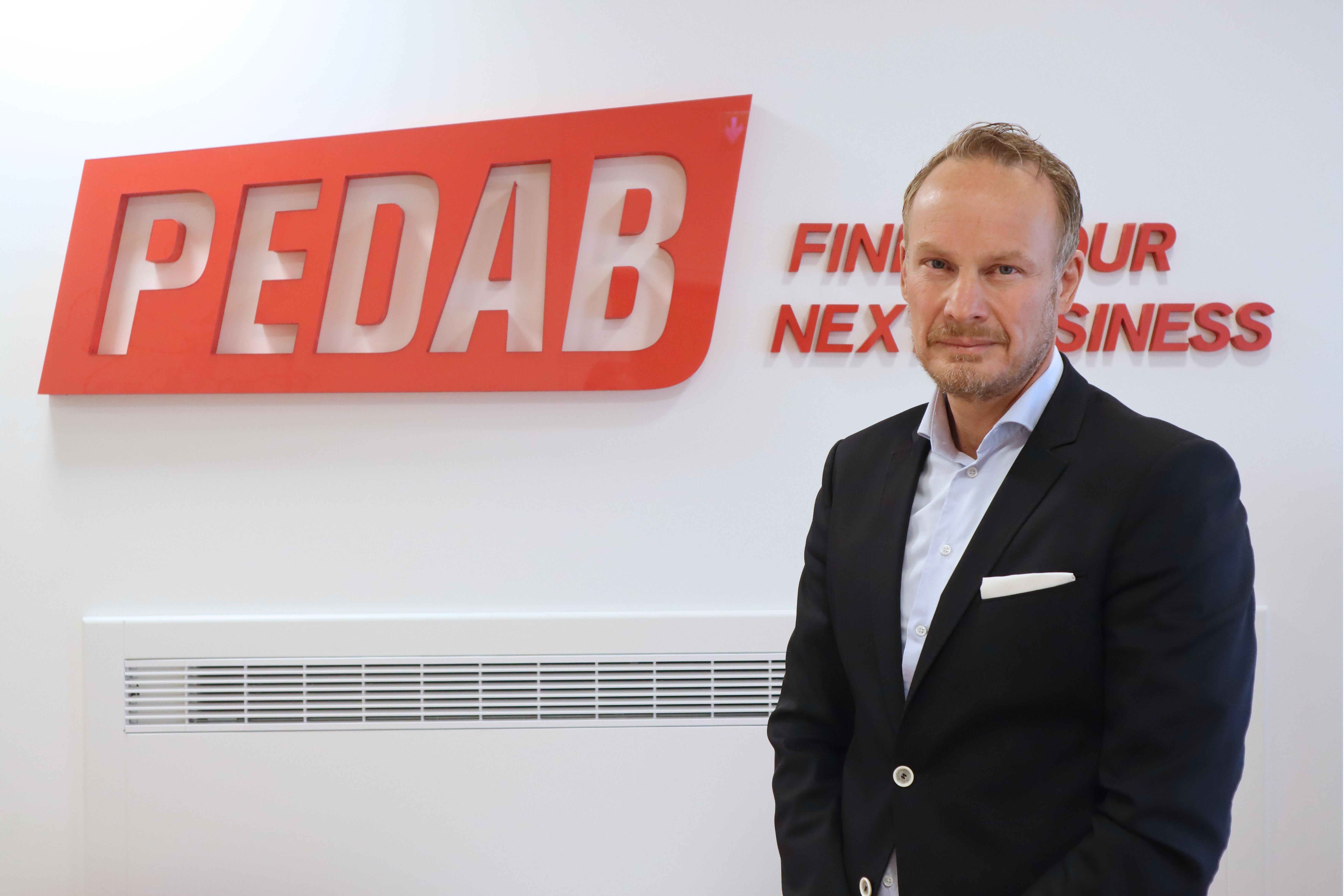 Kim Nordquelle foran hvit vegg med Pedab logo på.